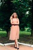 Mooi glimlachend meisje in een roze kleding op een achtergrond van groene bomen Royalty-vrije Stock Afbeelding