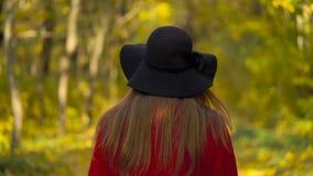 Mooi glimlachend meisje in een zwarte hoed met een geel esdoornblad op de achtergrond die in het Langzame de herfstbos lopen stock footage
