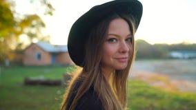 Mooi glimlachend meisje in een zwarte hoed met een zonsondergang op de achtergrond die in openlucht lopen stock video