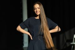 Mooi glimlachend meisje met lang recht haar in zwarte kleding stock foto
