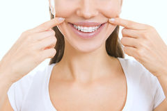 Mooi glimlachend meisje met pal die voor tanden op haar s richten stock foto