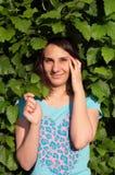 Mooi glimlachend meisje onder groene bladeren Stock Afbeelding