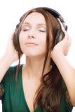 Mooi glimlachend meisje in oortelefoons royalty-vrije stock foto
