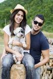 Mooi glimlachend paar dat hun witte hond koestert openlucht Royalty-vrije Stock Foto's