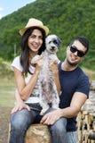 Mooi glimlachend paar dat hun witte hond koestert openlucht Stock Foto's