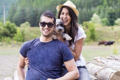 Mooi glimlachend paar dat hun witte hond koestert openlucht Stock Foto