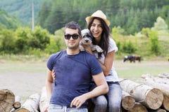 Mooi glimlachend paar dat hun witte hond koestert openlucht Royalty-vrije Stock Fotografie