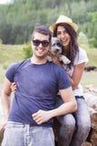 Mooi glimlachend paar dat hun witte hond koestert openlucht Royalty-vrije Stock Afbeeldingen