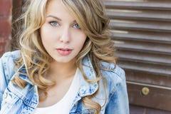 Mooi grappig blondemeisje met grote lippen die met een charmante glimlach, jeans en een wit overhemd dragen die in de stad lopen  Stock Foto