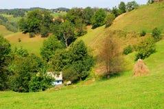Mooi groen heuvels en plattelandshuisje bij het platteland Royalty-vrije Stock Afbeeldingen
