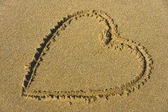 Mooi hart in zand bij het strand Stock Afbeelding