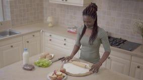 Mooi het glimlachen Afrikaans Amerikaans vrouwen rollend deeg met deegrol voor appeltaart op de moderne keuken Langzame Motie stock footage
