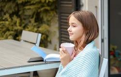 Mooi het glimlachen jong meisjesdagdromen met kop thee in haar handen en boek op lijst royalty-vrije stock foto's