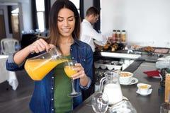 Mooi het glimlachen jong vrouwen dienend jus d'orange in glas bij een buffet in eetkamer van het hotel stock foto's