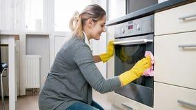 Mooi het glimlachen vrouwen doung huishoudelijk werk en schoonmakende keuken royalty-vrije stock afbeelding