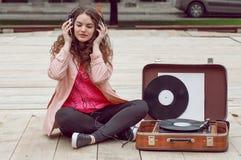 Mooi hipstermeisje met oude uitstekende vinylverslagen Luister aan muziek met emoties stock fotografie