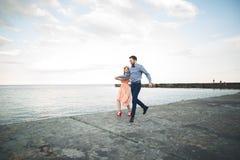 Mooi houdend van paar, trots die met lange kleding op pijler lopen royalty-vrije stock fotografie