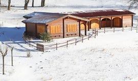 Mooi houten chalet in de bergen en sneeuw allen rond Royalty-vrije Stock Fotografie