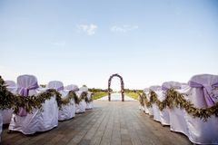 Mooi Huwelijk De ronde boog is verfraaid met bloemen en groen, de ceremonie op de kust De gaststoelen zijn verfraaid stock foto's