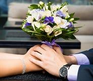 Mooi huwelijksboeket in bruiden en bruidegomshanden Stock Foto