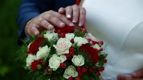 Mooi huwelijksboeket in de handen van de bruid en de bruidegom stock video
