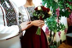 Mooi huwelijksboeket van wit en van Bourgondië rozen, bruid` s handen met trouwringen in borduurwerk stock foto's