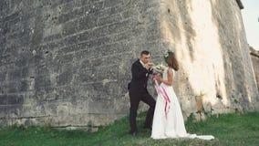 Mooi huwelijkspaar dichtbij het en kasteel die kussen glimlachen 4K stock videobeelden