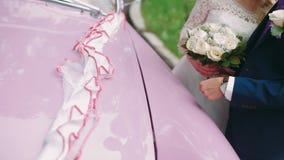 Mooi huwelijkspaar die dichtbij roze retro auto koesteren stock videobeelden