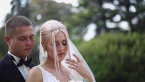 Mooi huwelijkspaar die in het park lopen Bruid met lange witte kleding en modieuze bruidegom stock footage