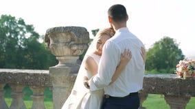 Mooi huwelijkspaar die in park dichtbij het kasteel omhelzen 4K stock footage
