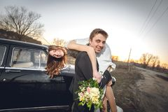 Mooi huwelijkspaar in het platteland naast de retro auto de mensenbruidegom neemt holdingsbruid in zijn wapens glimlachende geluk Royalty-vrije Stock Afbeelding