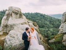 Mooi huwelijkspaar op prachtig rotsachtig landschap van de bergenachtergrond van de Karpaten stock afbeelding