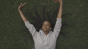 Mooi jong Afrikaans Amerikaans meisje die op het gras rusten Hoogste mening stock footage