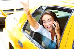 Mooi jong bedrijfswijfje dat op celtelefoon spreekt in taxi Royalty-vrije Stock Afbeeldingen