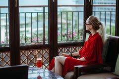 Mooi jong blondemeisje in rode kleding en zonnebril die rode cocktail van een glas op een open terras van drinken stock fotografie