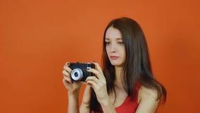 Mooi jong bruin-haired meisje met een in hand camera emoties Kunstportret in een studio op een oranje achtergrond stock footage