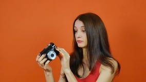Mooi jong bruin-haired meisje met een in hand camera emoties Kunstportret in een studio op een oranje achtergrond stock video