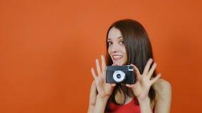 Mooi jong bruin-haired meisje met een in hand camera emoties Kunstportret in een studio op een oranje achtergrond stock videobeelden