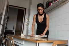 Mooi jong brunette die eigengemaakte verse deegwaren voorbereiden stock fotografie