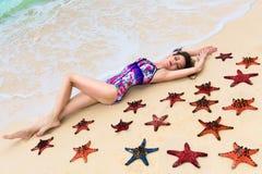 Mooi jong brunette die van de zon op de tropische kust genieten Royalty-vrije Stock Afbeelding