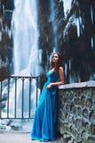 Mooi jong brunette in een blauwe kleding op een achtergrond van een gletsjer en een massief Stock Foto