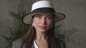 Mooi jong brunette in een elegant hoed en een pak stock videobeelden