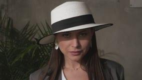 Mooi jong brunette in een elegant hoed en een pak stock video