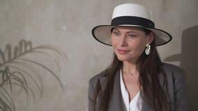 Mooi jong brunette in een elegant hoed en een pak stock footage
