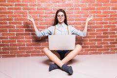 Mooi jong donker-haired meisje in vrijetijdskleding die met laptop op sholders stellen Royalty-vrije Stock Foto's