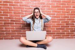 Mooi jong donker-haired meisje in vrijetijdskleding met laptop stock afbeelding