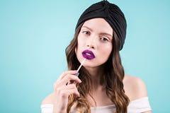 Mooi jong donkerbruin model die lippenstift op blauwe achtergrond, exemplaarruimte toepassen Manier, purpere kleur, manierportret royalty-vrije stock afbeeldingen