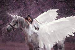 Mooi, jong elf, die met een eenhoorn lopen Zij draagt een ongelooflijke lichte, witte kleding Kunsthotography royalty-vrije stock foto's