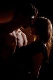 Mooi jong en paar die geïsoleerd op zwarte achtergrond koesteren kussen Royalty-vrije Stock Foto's