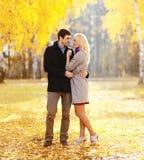 Mooi jong houdend van paar die in de zonnige herfst koesteren stock afbeelding